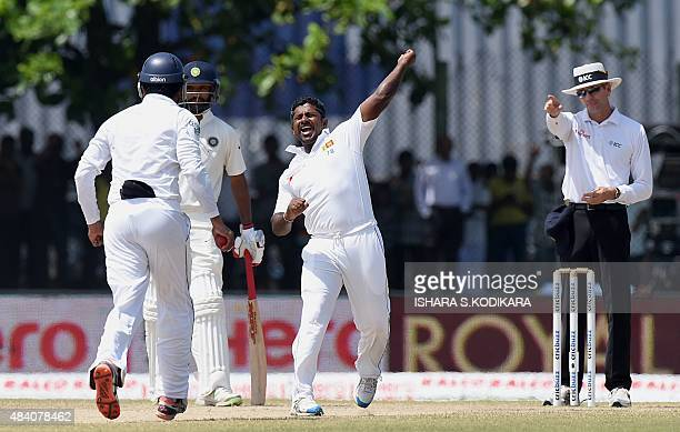 Sri Lankan cricketer Rangana Herath celebrates after dismissing unseen Indian batsman Ishant Sharma during the fourth day of the opening Test match...