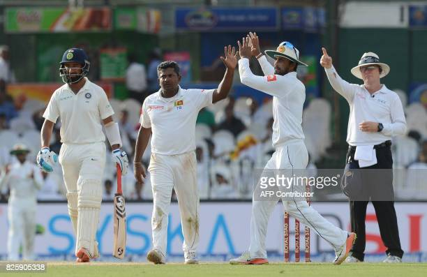 Sri Lankan cricketer Rangana Herath celebrates with his captain Dinesh Chandimal after on field umpire gave out Indian cricketer Lokesh Rahul during...