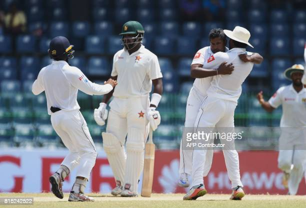 Sri Lankan cricketer Rangana Herath celebrates with his teammates after he dismissed Zimbabwe's cricketer Tarisai Musakanda during the Third day of...