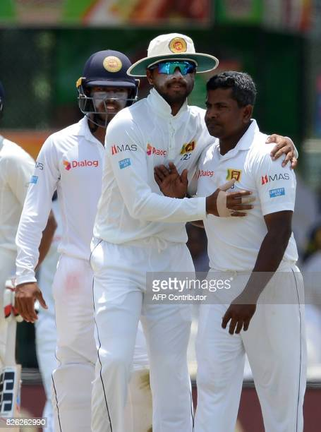 Sri Lankan cricketer Rangana Herath celebrates with his teammates after he dismissed Indian cricketer Ravichandran Ashwin during the second day of...