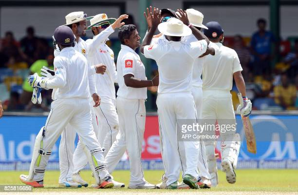 Sri Lankan cricketer Rangana Herath celebrates with teammates after dismissing Indian cricket captain Virat Kohli during the first day of the second...