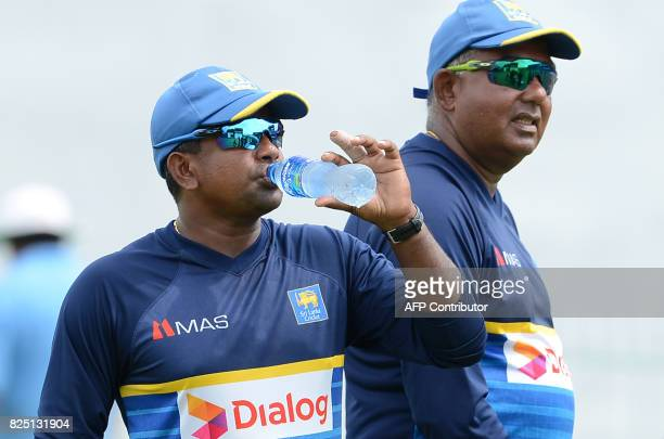 Sri Lankan cricketer Rangana Herath drinks water as cricket manager Asanka Gurusinghe looks on during a practice session at the Sinhalease Sports...