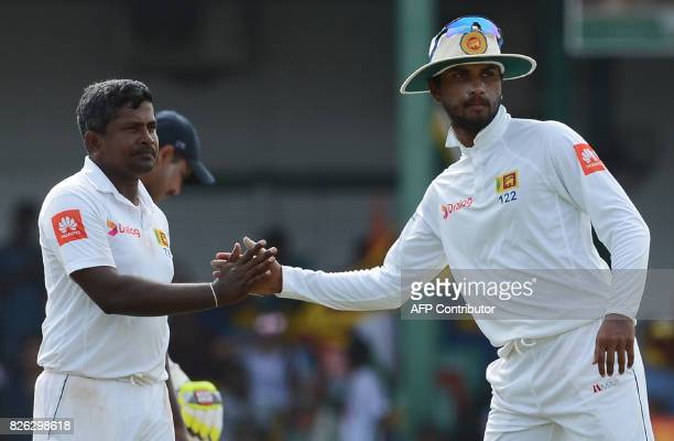 Sri Lankan cricketer Rangana Herath is congratulated by his captain Dinesh Chandimal after dismissing Indian cricketer Mohammed Shami during the...