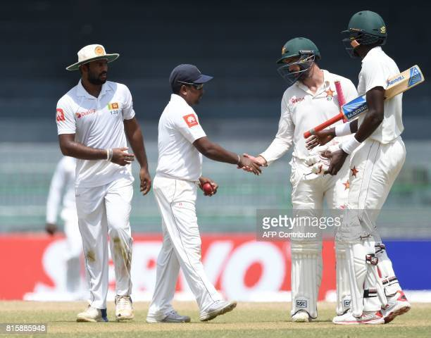 Sri Lankan cricketer Rangana Herath is congratulated by Zimbabwe cricket captain Graeme Cremer during the fourth day of the only oneoff Test match...