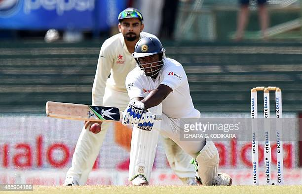 Sri Lankan cricketer Rangana Herath plays a shot as Indian cricket team captain Virat Kohli looks on during the third day of their third and final...