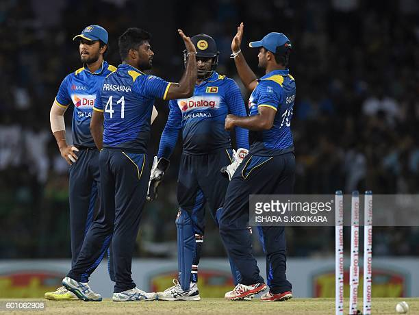Sri Lankan cricketer Seekkuge Prasanna celebrates with teammates after he dismissed Australia's Glenn Maxwell during the final T20 international...