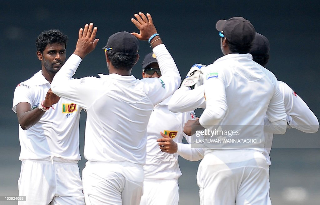 Sri Lankan cricketer Shaminda Eranga (L) celebrates with his teammates after dismissing unseen Bangladeshi cricketer Tamim Iqbal during the third day of the second Test match between Sri Lanka and Bangladesh at the R. Premadasa Cricket Stadium in Colombo on March 18, 2013.