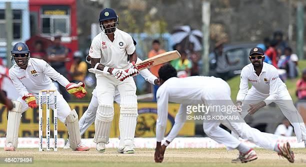 Sri Lankan cricketer Tharindu Kaushal takes a catch to dismiss Indian batsman Shikhar Dhawan as Sri Lankan wicketkeeper Dinesh Chandimal looks on...