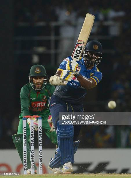 Sri Lankan cricketer Thisara Perera is watched by Bangladesh wicketkeeper Mushfiqur Rahim as he plays a shot during the second T20 international...