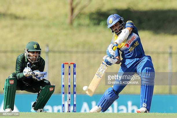 Sri Lankan cricketer Tillakaratne Dilshan is watched by Pakistani wicketkeeper Sarfraz Ahmed as he plays a shot during the fifth and final one day...
