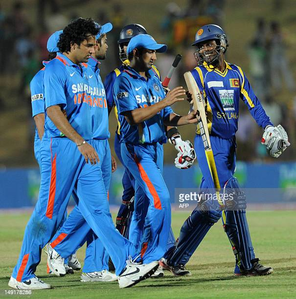 Sri Lankan cricketer Upul Tharanga and Indian cricketer Gautam Gambhir inspect a bat as Indian cricketers Virat Kohli and Zaheer Khan look on after...