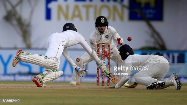 Sri Lankan cricketer Upul Tharanga dives in as Indian Wicket keeper Wriddhiman Saha awaits for the ball to complete a successful run out chance the...