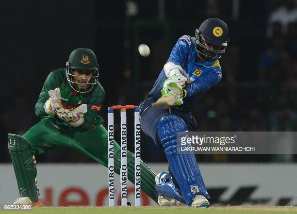 Sri Lankan cricketer Upul Tharanga is watched by Bangladesh wicketkeeper Mushfiqur Rahim as he plays a shot during the second T20 international...