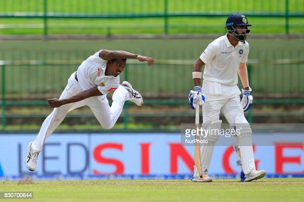 Sri Lankan cricketer Vishwa Fernando delivers a ball as India's Lokesh Rahul looks on during the 1st Day's play in the 3rd Test match between Sri...