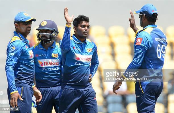 Sri Lankan cricketer Wanidu Hasaranga celebrates with his teammates after he dismissed Zimbabwe cricketer Craig Ervine during the third oneday...