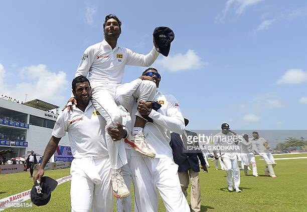 Sri Lankan cricketers carry Kumar Sangakkara on their shoulders as they walk around the field to celebrate their win over India by 63 runs on the...