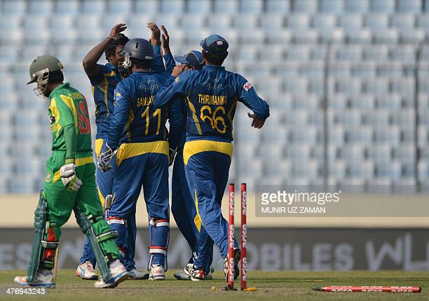 Sri Lankan cricketers celebrate after the dismissal of Bangladesh cricketer Mominul Haque during the tenth match of the Asia Cup oneday cricket...