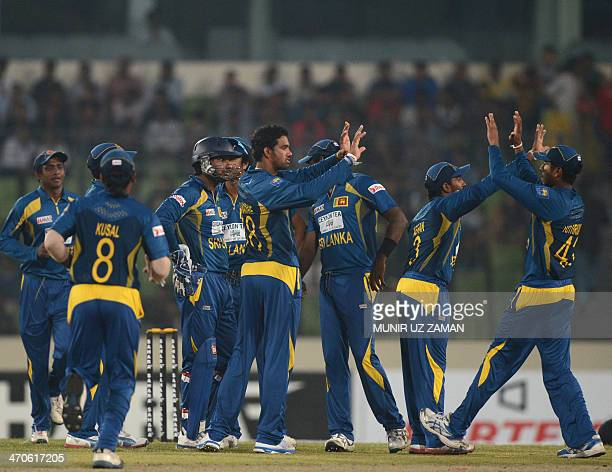 Sri Lankan cricketers celebrate after the dismissal of Bangladeshi batsman Mominul Haque during the second OneDay International cricket match between...