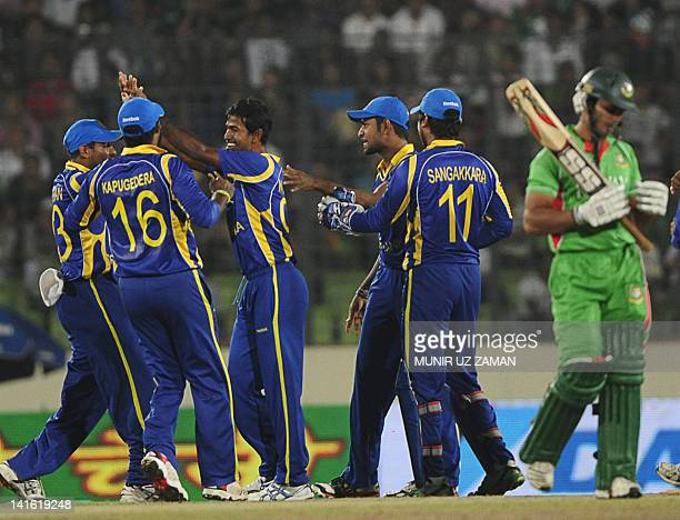 Sri Lankan cricketers celebrate after the dismissal of the Bangladeshi batsman Nazim Uddin during the one day international Asia Cup cricket match...