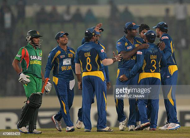 Sri Lankan cricketers celebrate their win as Bangladeshi batsman Arafat Sunny looks on following the second OneDay International cricket match...