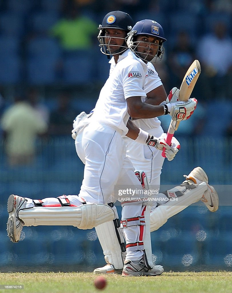 Sri Lankan cricketers Kumar Sangakkara (L) and Dinesh Chandimal run between wickets during the second day of the second Test match between Sri Lanka and Bangladesh at the R. Premadasa Cricket Stadium in Colombo on March 17, 2013.