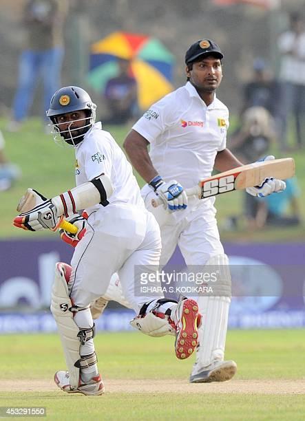 Sri Lankan cricketers Kumar Sangakkara and Kaushal Silva run between wickets during the second day of the opening Test match between Sri Lanka and...