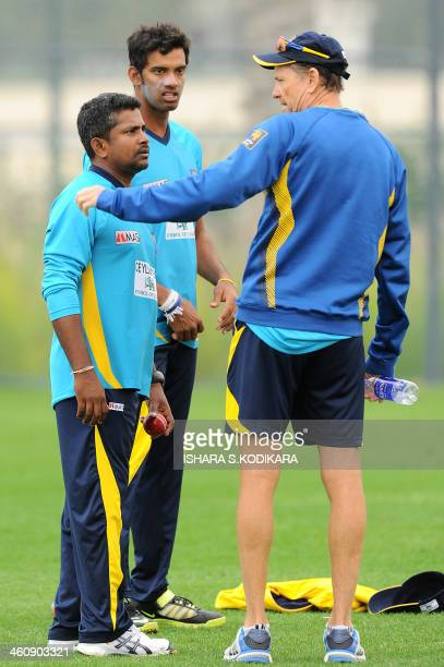 Sri Lankan cricketers Rangana Herath and Sachithra Senanayake speak with team coach Graham Ford during a practice session at the Dubai Sports city in...