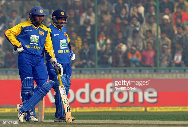 Sri Lankan cricketers Sanath Jayasuriya and Thilan Thushara watch as the sightscreen is adjusted during the fifth and final One Day International...
