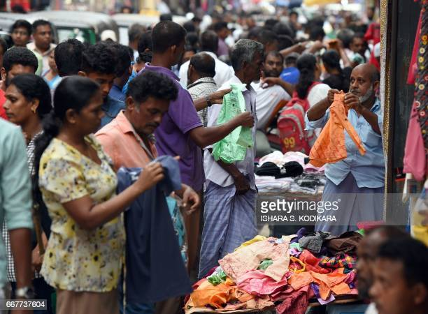 A Sri Lankan customer peruses clothing at a stall at a market in Colombo on April 12 ahead of the traditional Sinhala and Tamil New Year Sri Lanka...