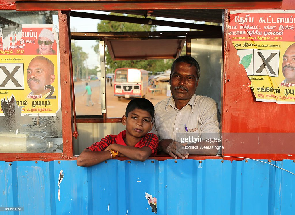 Sri Lankan ethnic Tamil man and her son look out posters pasted road side shop at the former rebel capital of Kilinochchi on September 15 2013 in...