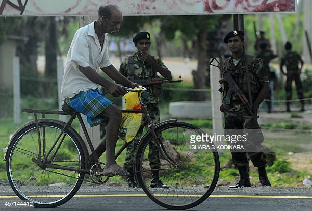 A Sri Lankan ethnic Tamil man rides a bicycle past soldiers in Jaffna on October 13 as Sri Lankan President Mahinda Rajapake visited the town to...