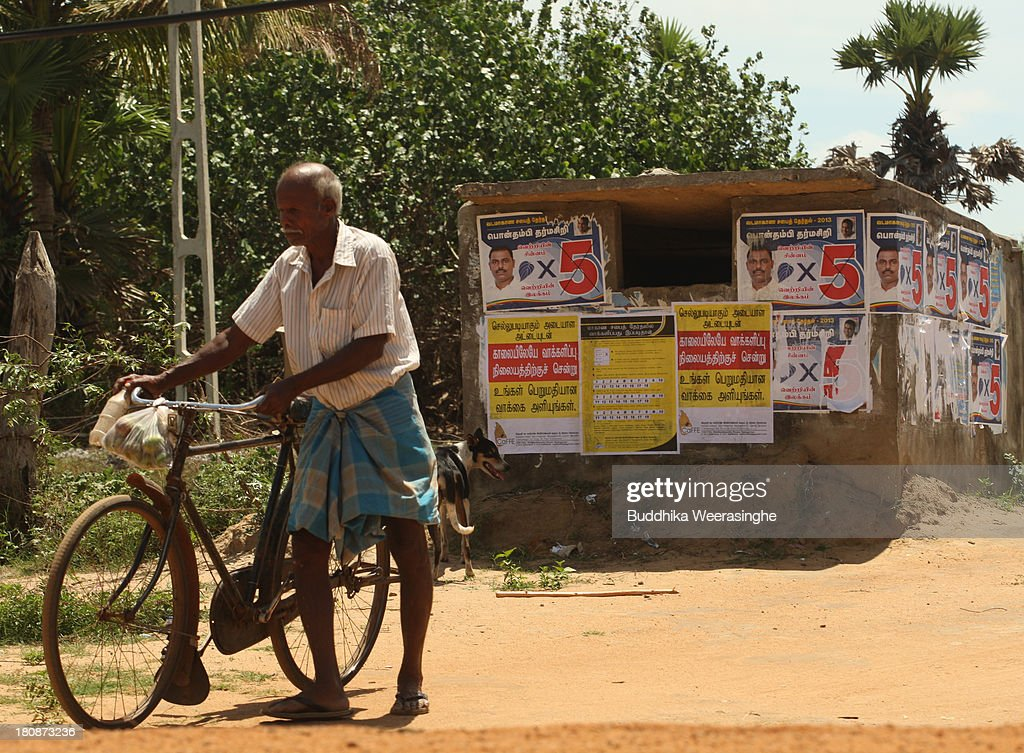 Sri Lankan ethnic Tamil man walks beside the upcoming election campaign posters on a wall at former rebel capital on September 17 2013 in Kilinochchi...