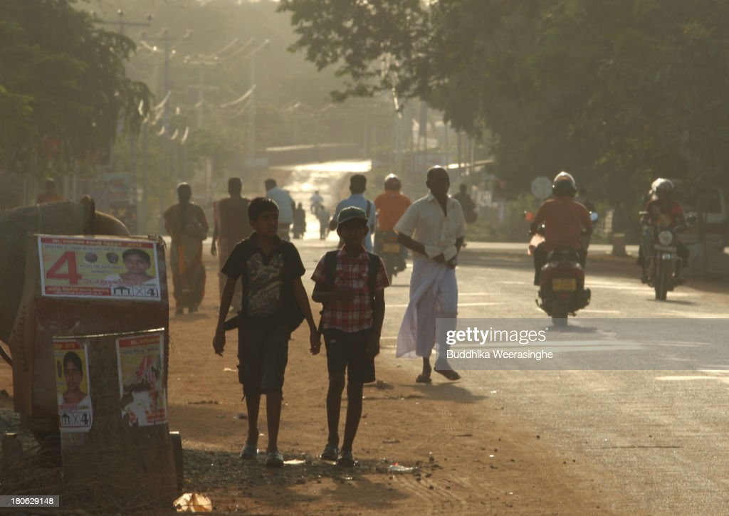 Sri Lankan ethnic Tamil people walk past up coming election campaign posters of Tamil National Alliance party candidate at the former rebel capital...