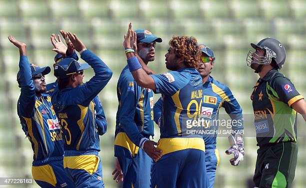 Sri Lankan fielders congratulate bowler Lasith Malinga for taking the wicket of Pakistani batsman Ahmed Shehzad during the final match of the Asia...