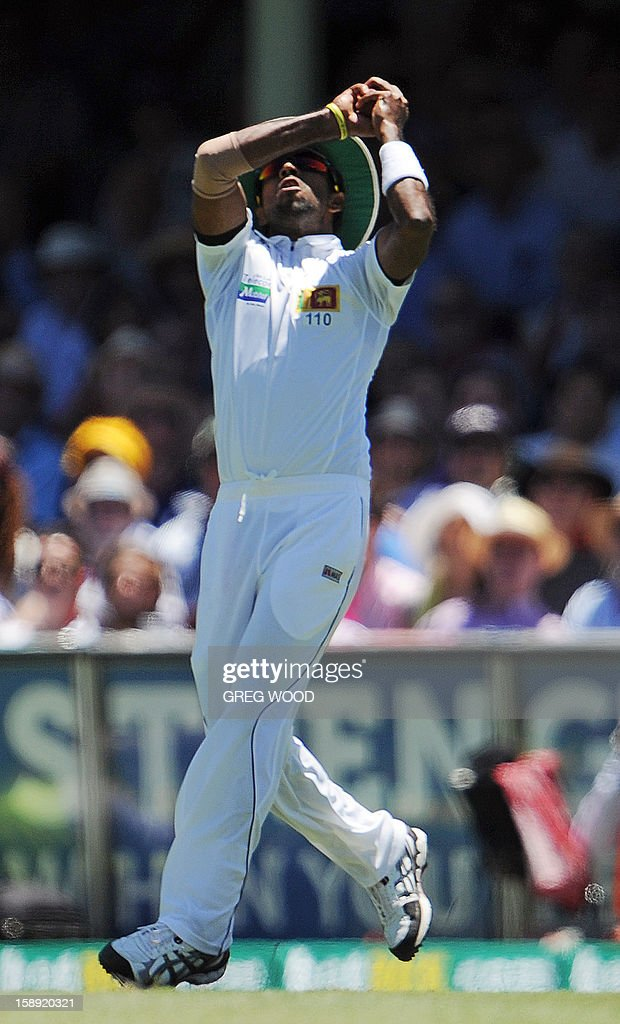 Sri Lankan fieldsman Dhammika Prasad takes an outfield catch to dismiss Australian batsman David Warner on day two of the third cricket Test between Sri Lanka and Australia at the Sydney Cricket Ground on January 4, 2013. IMAGE STRICTLY RESTRICTED TO EDITORIAL USE - STRICTLY NO COMMERCIAL USE AFP PHOTO / Greg WOOD