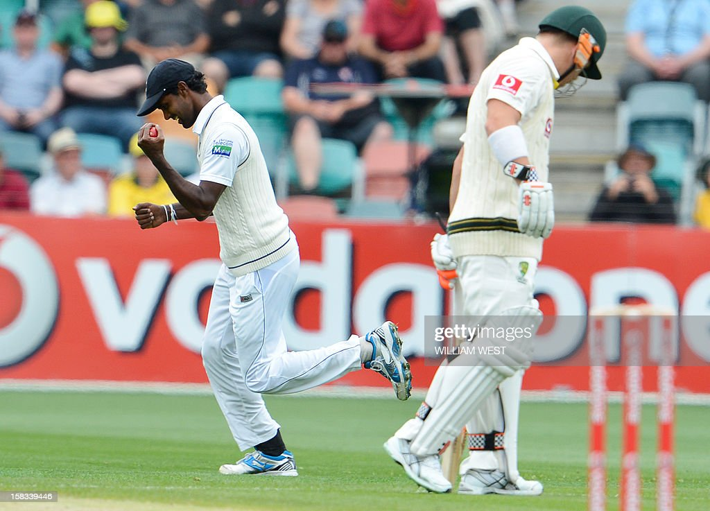 Sri Lankan fieldsman Shaminda Eranga (L) celebrates catching Australian batsman Ed Cowan as his teammate David Warner (R) looks away on the first day of the first cricket Test match in Hobart on December 14, 2012. AFP PHOTO/William WEST IMAGE