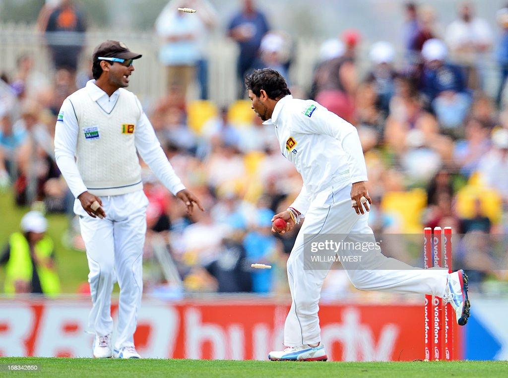 Sri Lankan fieldsman Tillakaratne Dilshan (R) runs out Australian batsman David Warner as teammate Kumar Sangakkara (L) celebrates on the first day of the first cricket Test match, in Hobart on December 14, 2012. AFP PHOTO/William WEST IMAGE