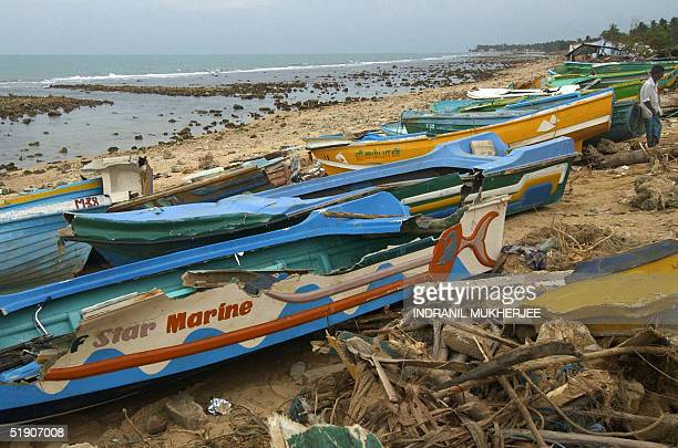 Sri Lankan fisherman stands beside damaged fishing boats on a tsunami destroyed beach at Point Pedro the countries northern most point some 440 kms...