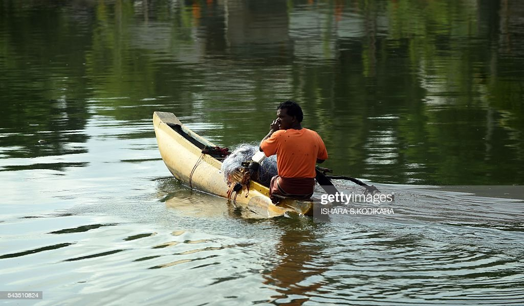 A Sri Lankan fishermen paddles a canoe along the shoreline in Colombo on June 29, 2016. / AFP / ISHARA