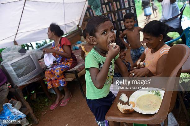 A Sri Lankan flood affected boy eats a meal at a road camp in Kelaniya suburb of the capital Colombo on May 18 2016 Rescue workers on May 18...