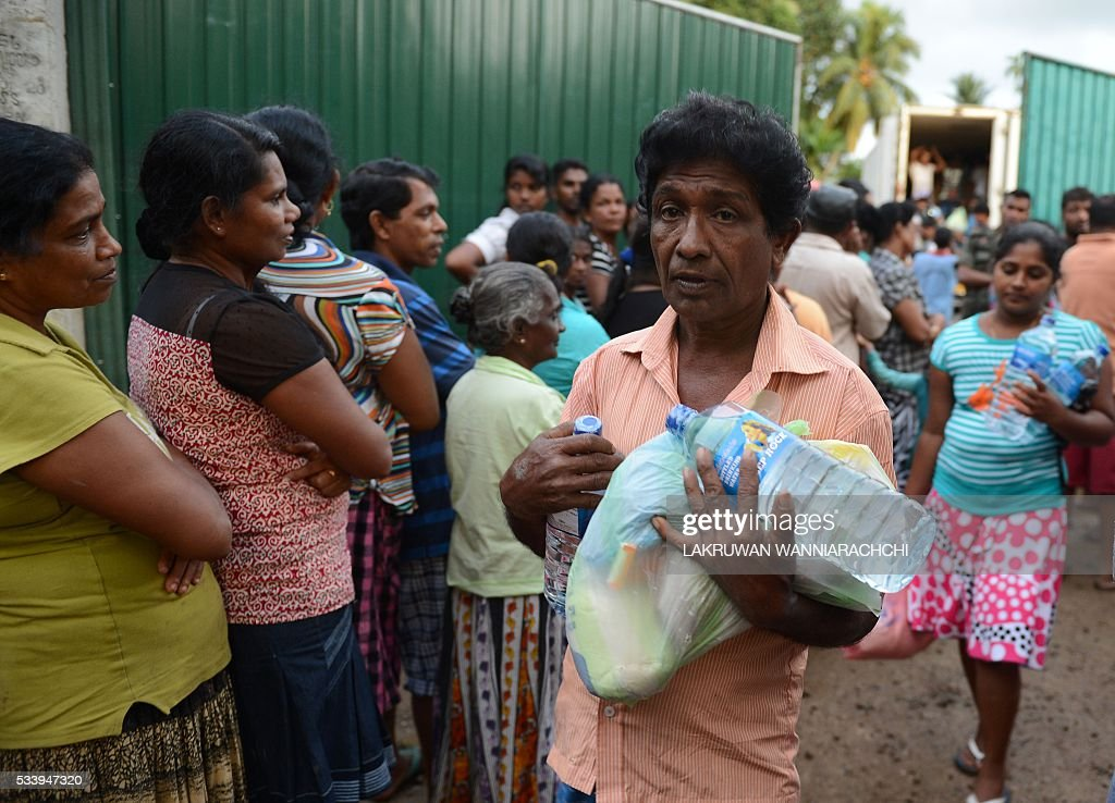 Sri Lankan flood affected residents line up to receive food in the Colombo suburb of Kaduwela on May 24, 2016. Floodwaters are subsiding across Sri Lanka revealing the full extent of damage from last week's heavy rains that also triggered landslides, officials said as the death toll crossed 100. / AFP / LAKRUWAN
