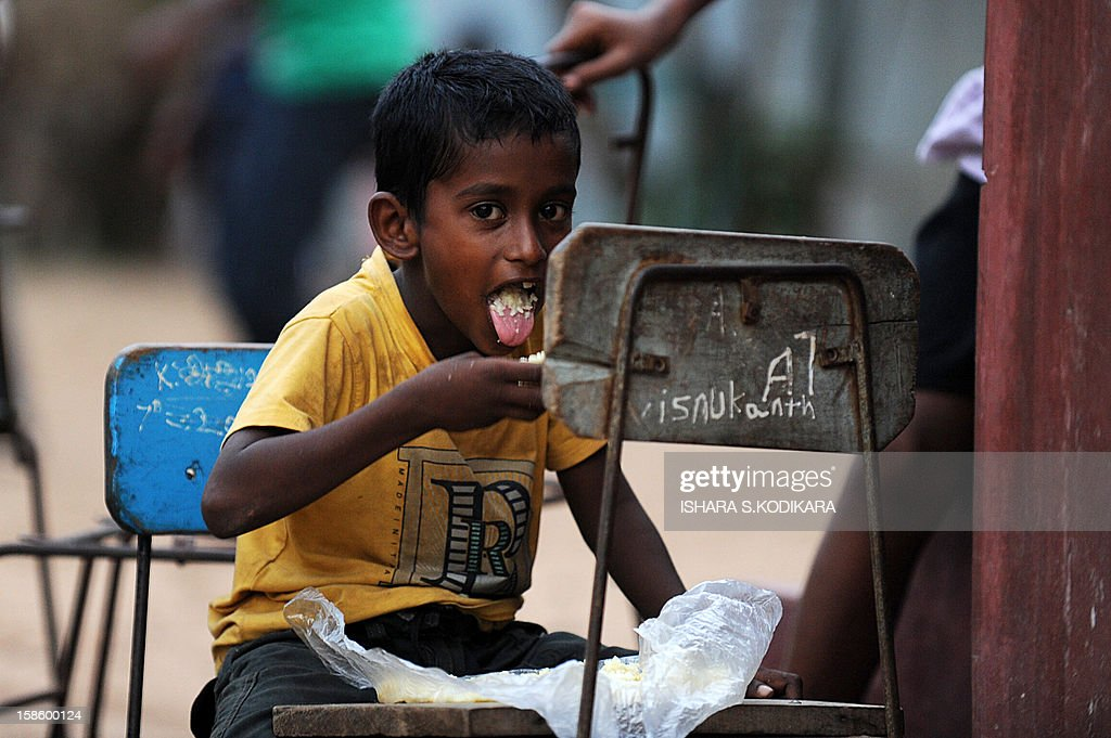 A Sri Lankan flood affected victim eats in a makeshift camp in the north western province town of Chilaw on December 20, 2012. Flash floods have killed at least 25 people in Sri Lanka and left more than a quarter of a million marooned in their homes, disaster officials said. Heavy rains, which have battered the island for much of the week, were still being reported in 14 of Sri Lanka's 25 administrative districts, with the central highlands -- one of the world's key tea producing regions -- the worst hit. AFP POHOTO/ Ishara S.KODIKARA