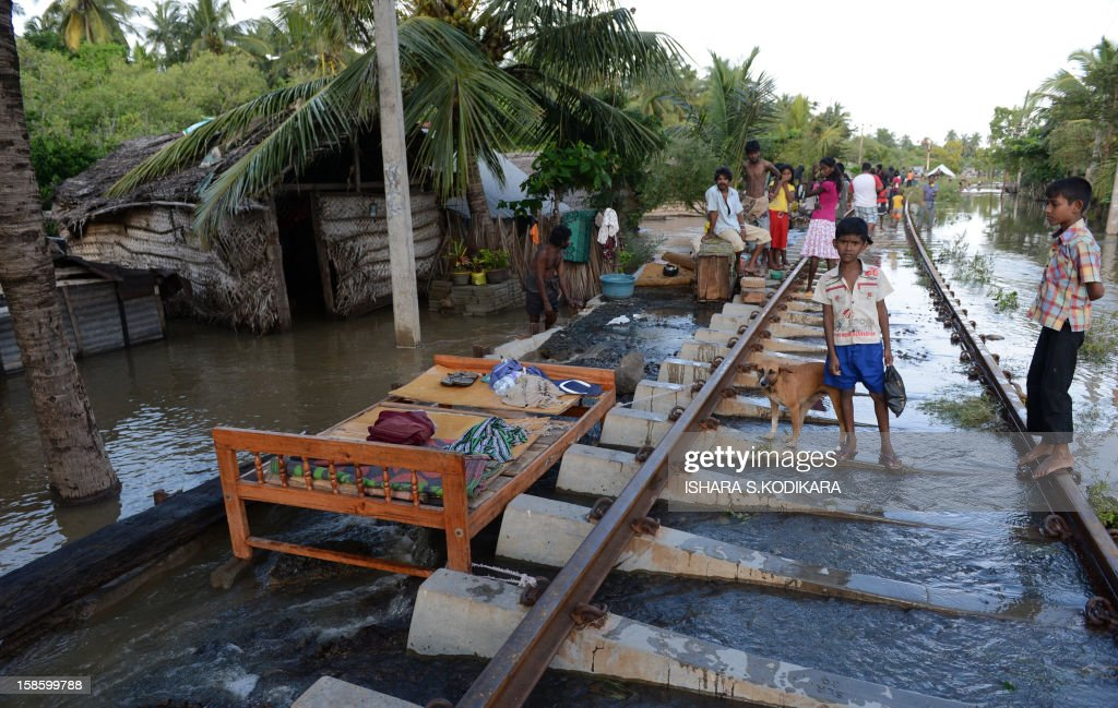Sri Lankan flood affected victims stand on railroad tracks in the north western province town of Chilaw on December 20, 2012. Flash floods have killed at least 25 people in Sri Lanka and left more than a quarter of a million marooned in their homes, disaster officials said. Heavy rains, which have battered the island for much of the week, were still being reported in 14 of Sri Lanka's 25 administrative districts, with the central highlands -- one of the world's key tea producing regions -- the worst hit. AFP POHOTO/ Ishara S