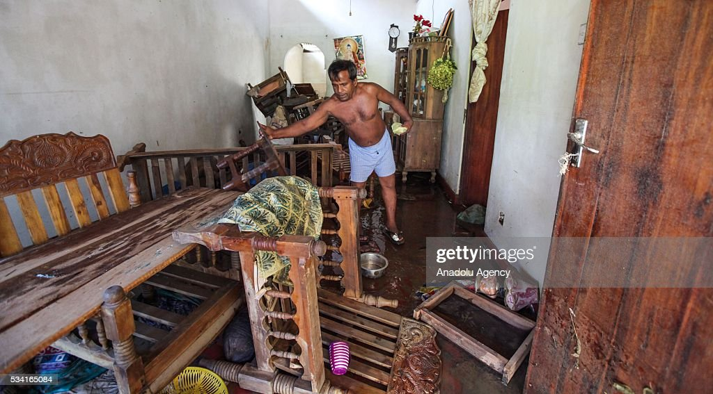 A Sri Lankan flood victim cleans his house as the water level starts to decline in Wellampitiya, outskirts of Colombo, Sri Lanka, Wednesday, May 25, 2016.