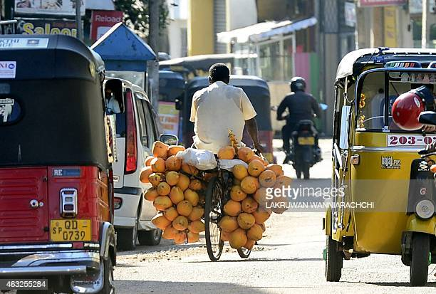 A Sri Lankan fruit vendor selling king coconuts rides his bicycle in Colombo on February 12 2015 Sri Lanka's new government will seek loans exceeding...
