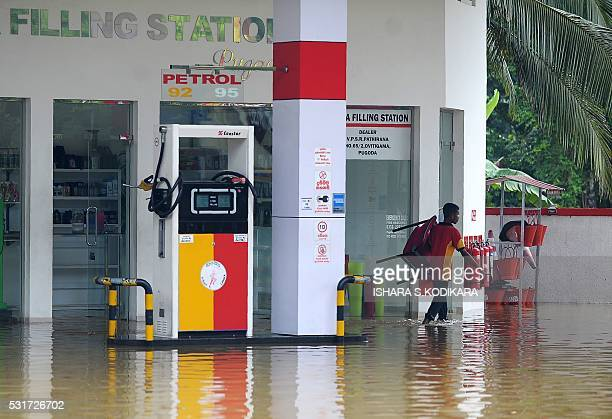 A Sri Lankan gasstation worker walks through a flooded forecourt following rains in Pugoda on May 16 2016 Floods and landslides in Sri Lanka have...