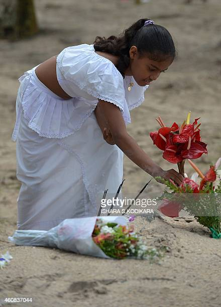 A Sri Lankan girl commemorates the victims of the December 2004 tsunami offering flowers prayers and alms during a special ceremony to mark the tenth...