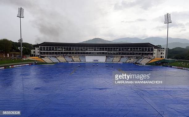 Sri Lankan groundstaff cover the pitch with plastic sheeting after rain showers during the first day of the opening Test match between Sri Lanka and...