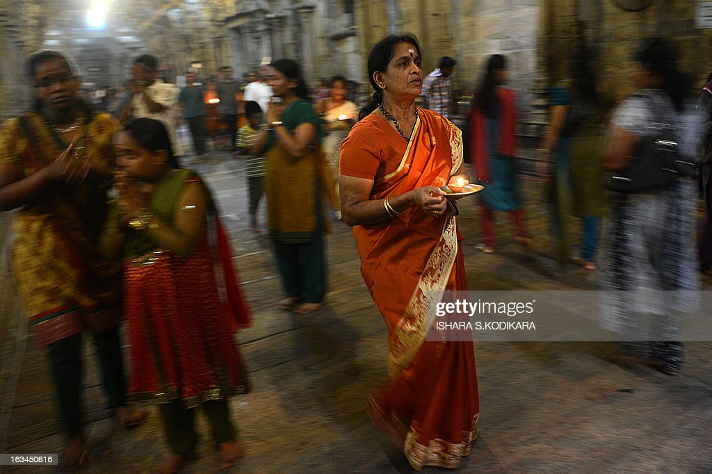 A Sri Lankan Hindu devotee offers prayers while holding an oil lamp during the Maha Shivaratri festival at a temple in Colombo on March 10, 2013. The festival of Maha Shivaratri is marked by Hindus fasting and offering prayers in a night long vigil. AFP PHOTO/ Ishara S. KODIKARA