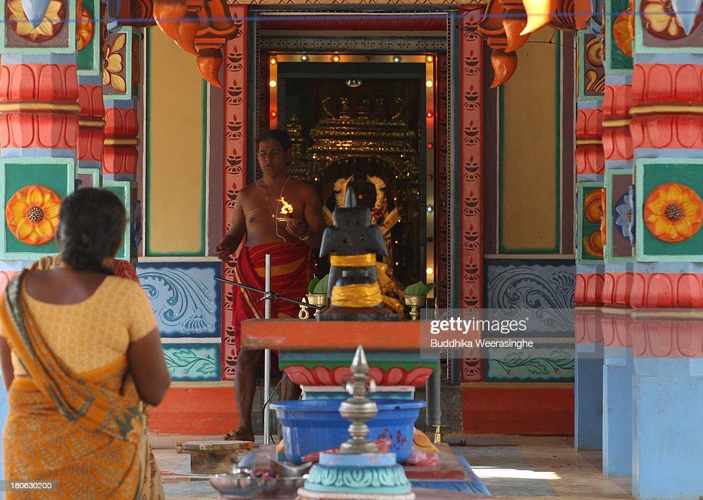 Sri Lankan Hindu priest performs ritual as woman pray at Hindu temple former rebel capital of Kilinochchi on September 15 2013 in Kilinochchi Sri...